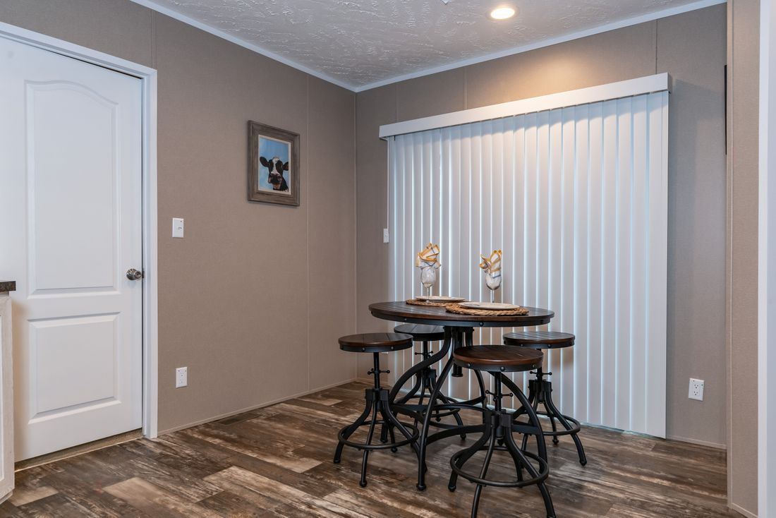 The THE ANNIVERSARY PLUS Dining Room. This Manufactured Mobile Home features 3 bedrooms and 2 baths.